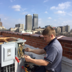 Fred's commercial AC repair technician fixing rooftop unit in city